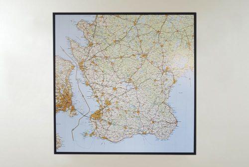 Väggkarta med ram över Skåne för markering med nålar.